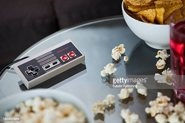 A vintage Nintendo NES controller photographed on a glass table surrounded by bowls of snacks taken on July 9 2013