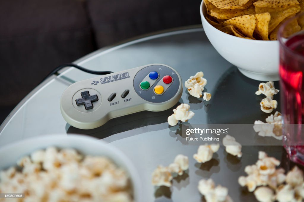 A vintage Nintendo SNES controller photographed on a glass table, surrounded by bowls of snacks, taken on July 9, 2013.