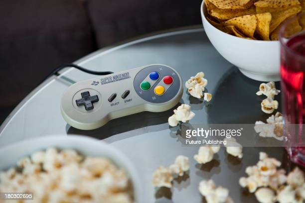 A vintage Nintendo SNES controller photographed on a glass table surrounded by bowls of snacks taken on July 9 2013
