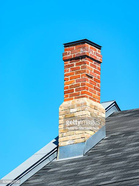 Vintage old red brick chimney in house during a blue clear sky day