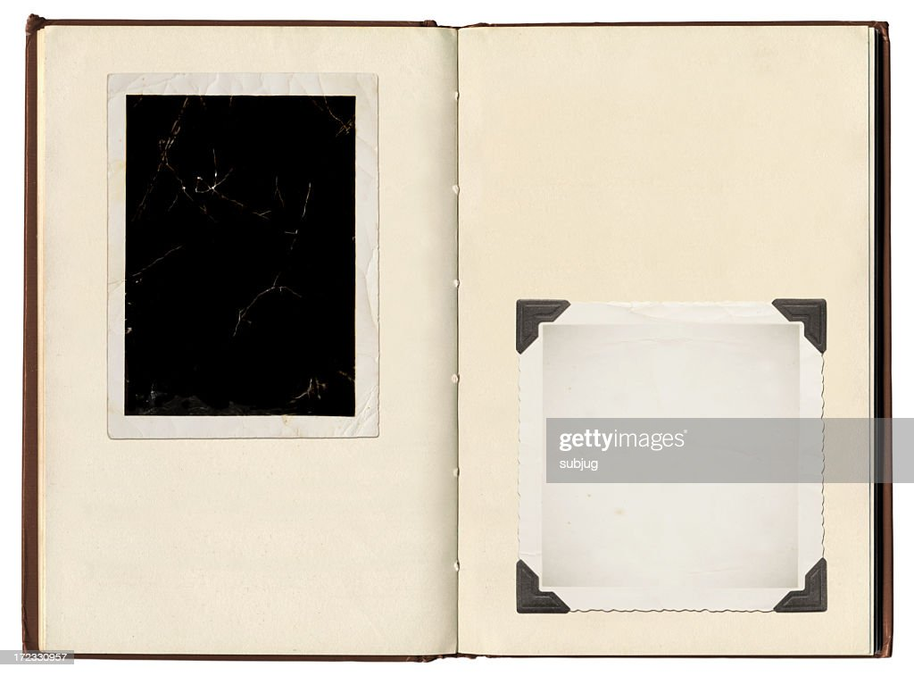 A vintage photo album with photo corners holding photos