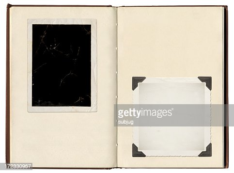 A vintage photo album with photo corners holding photos
