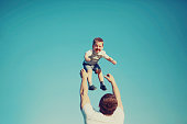Vintage photo happy father and child having fun outdoors, summer, sun, blue sky, family, travel, vacation, childhood, father's day - concept