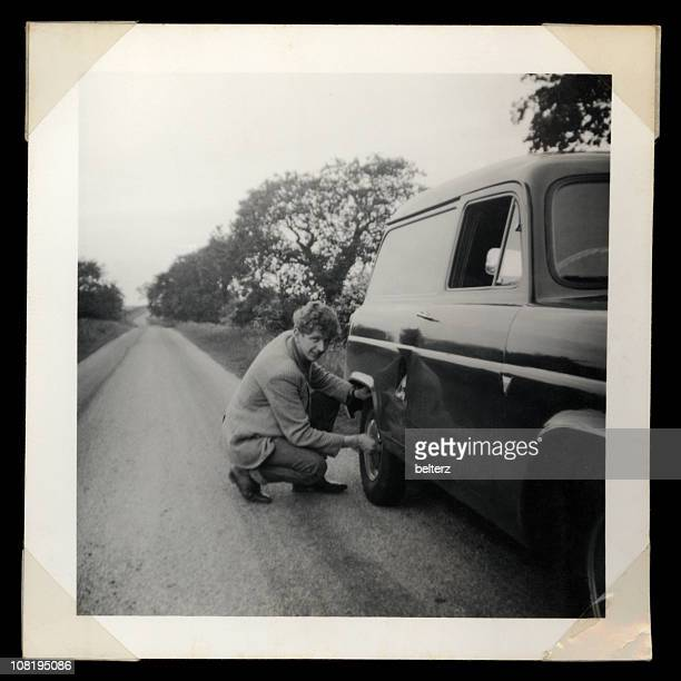 Vintage Photograph of Man Checking Rear Tire on Truck