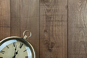 Vintage clock on a wood background. Part of clock showing. Time almost 12 o'clock. Vintage, traditional muted warm brown colors. Lots of copy