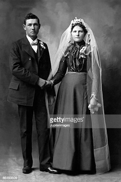 Vintage portrait of bride and groom holding hands