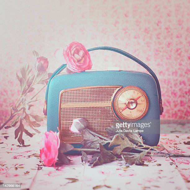 Vintage radio with pink flowers on table