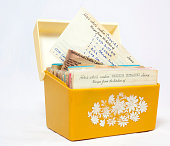 Old, yellow 1960s recipe box with handwritten recipes on index cards