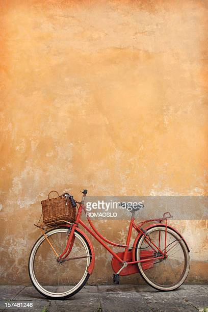 Vintage red bike leaning against a yellow wall in Tuscany