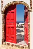View of the blue Aegean sea, as seen through a vintage red door ajar in the island of Santorini