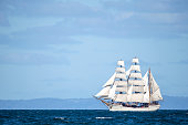 Vintage Clipper ship with full sail in the open ocean.