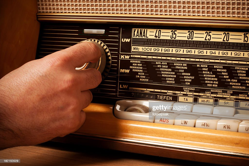 Vintage short wave radio with person's hand on the tuner : Stock Photo