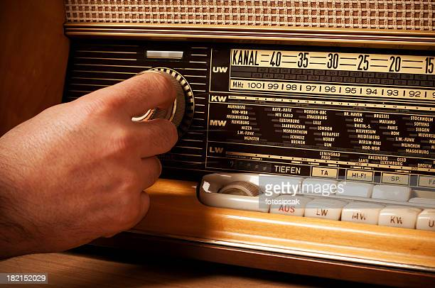 Vintage short wave radio with person's hand on the tuner