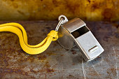 Vintage silver whistle on rusty metallic background. Referee trainer sport competition tool instrument, start finish stopping game and attention moments equipment. Close-up photo