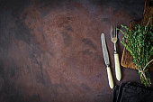Vintage silverware with ivory handle, dark textile, wooden cutting board and bunch of fresh thyme on dark rusty background. Top view, copy space for text.
