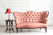 Pink vintage sofa and lamp on white wall.