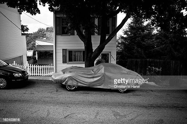 CONTENT] vintage sports car covered under a tarp in front of a small home on a small street in suburbia Pittsburgh PA