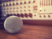Vintage style photo of the microphone in a recording studio or concert hall with amplifier equipment in out of focus background. : Vintage style and filtered process.