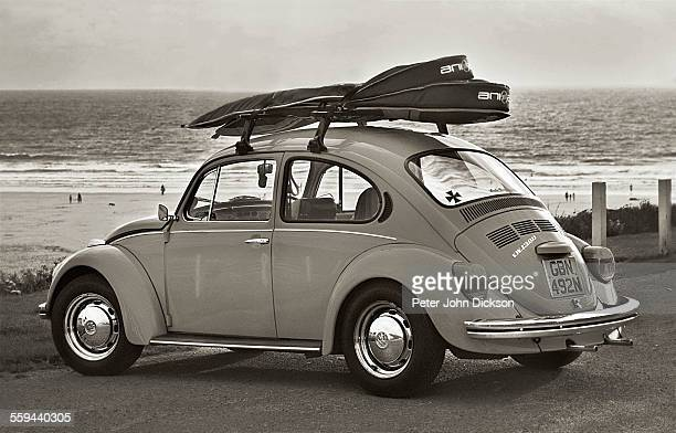 A vintage style Volkswagen Beetle is parked overlooking the the beach at Woolacombe Devonshire UK On the roof rack is two surfboards June 2012