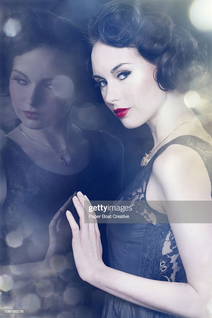vintage styled lady leaning against a mirror : Stock Photo