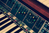Abstract toned image of vintage synthesizer keyboard musical instrument. Selective focus and tilt.