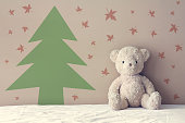 vintage teddy bear sit on the right side white bed at headboard and brown flat wall with green christmas tree and red maple leaf paint winter feel background for gift and surprise