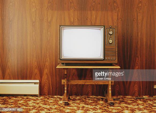 Vintage television on stand, against wood panel wall