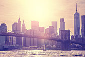 Vintage toned sunset over Manhattan and Brooklyn Bridge, New York City, USA.