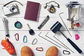 vintage travel equipment for holiday passport, boots, lantern, wick, knife, camera, tripod, compass, clock, hammer, car key, carabiner, anchor and tent rope on white wood floor or table top view