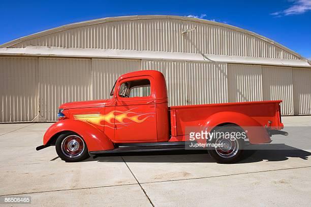 Vintage truck parked next to hangar