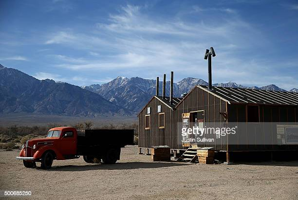 A vintage truck sits parked in front of a replica of an internment camp mess hall at Manzanar National Historic Site on December 9 2015 near...