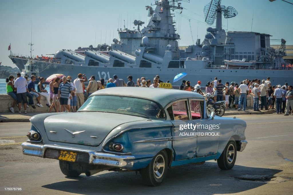 A vintage US-made car passes by as Cubans wave at the 'Moskva' Russian guide missile cruiser arriving at Havana's harbour, on August 3, 2013. The vessel is part of a three-ship group in official visit to Cuba. AFP PHOTO/Adalberto ROQUE