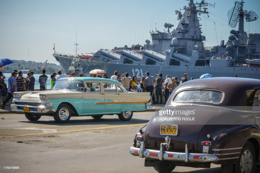 Vintage US-made cars pass by as Cubans watcht the 'Moskva' Russian guide missile cruiser arriving at Havana's harbour, on August 3, 2013. The vessel is part of a three-ship group in official visit to Cuba. AFP PHOTO/Adalberto ROQUE