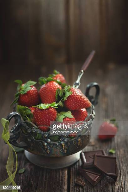 Vintage vase of strawberries with green ribbon on wooden table.