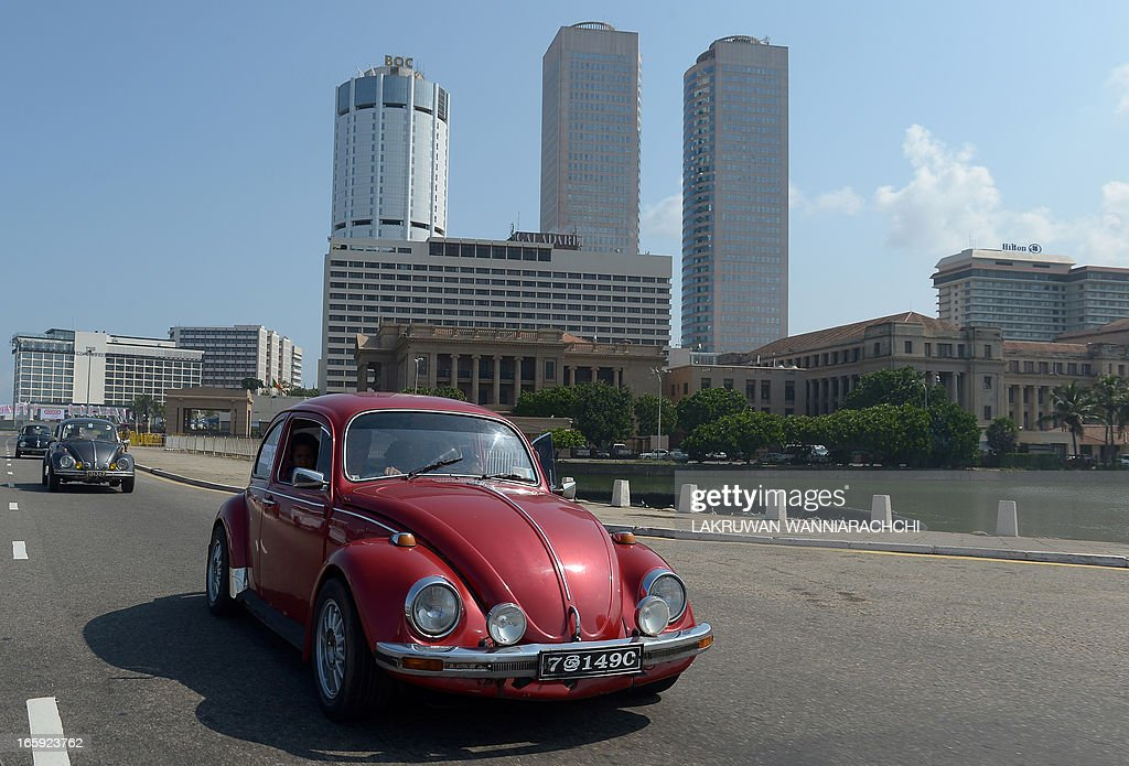 A vintage Volkswagen Beetle car drives down a road during Volkswagen owner's club ' pride of ownership' diamond jubilee rally 2013 in Colombo on April 7, 2013. Volkswagen owners hold an annual pageant in Sri Lanka to show off their vintage cars.