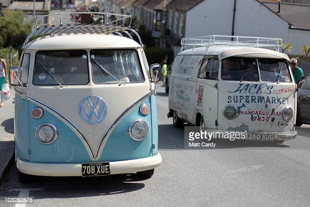 A vintage VW van passes a VW campervan parked near Fistral beach at the site of the Newquay Relentless Boardmasters festival on August 5 2010 in...
