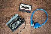Vintage walkman, cassete and headphones on the wooden background