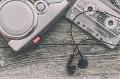 Vintage walkman cassette player with earbuds and tape cassette, retro style toned image