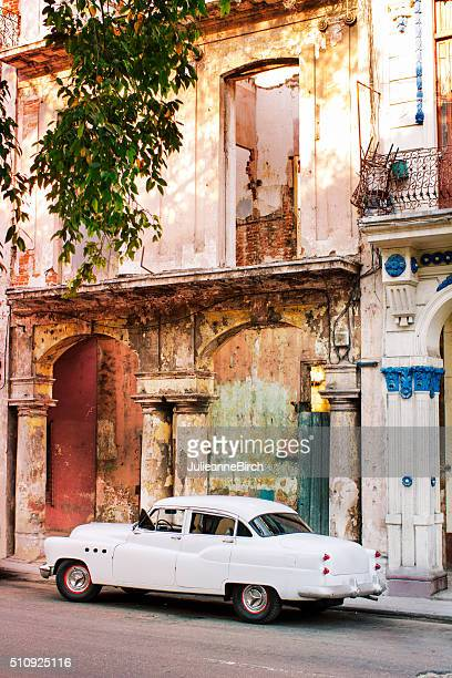 Vintage white car in colourful Cuban street