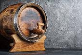 Vintage wooden barrel with tap in dark cellar on gray concrete background