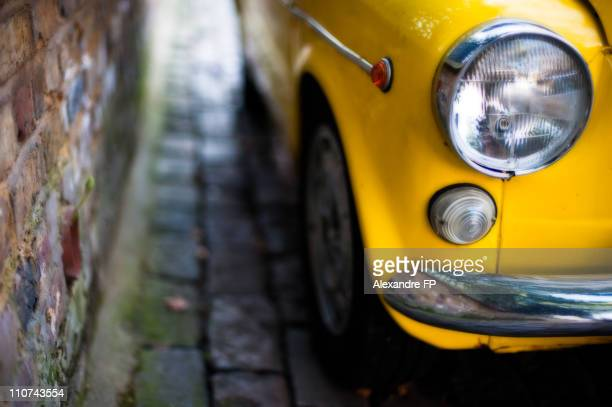 Vintage yellow car parked in cobblestones street