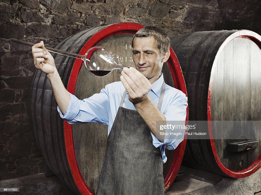 A vintner studies red wine in a wine thief