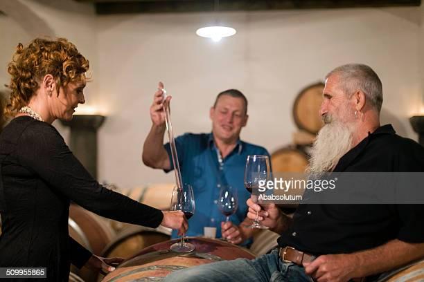 Vinaio prendendo il campione di vino rosso nella vecchia cantina, Europa.