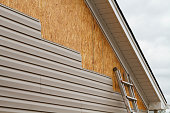 New beige vinyl siding being installed over an osb (oriented strand board) substrate on a residential house in the Southeastern USA region on a cloudy day. The old vinyl siding was being replaced afte