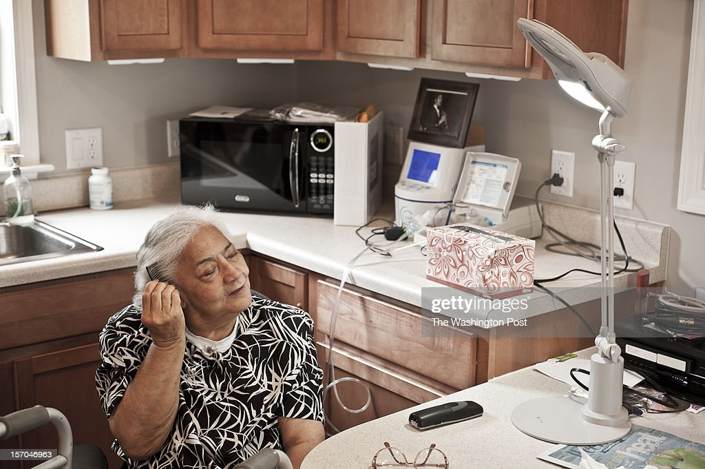 Viola Baez, 86, combs her hair under a futuristic-looking light in the living room of her med-cottage, the first in Alexandria, VA, on Friday, July 20, 2012. Baez was apprehensive about moving into the one-room addition to her family's Vengo Ct. home, which is outfitted with remote-controlled cameras to monitor her health. As the weeks went by, she settled into the stain-resistant space. Baez now spends most days curled on a hide-a-bed, with a newspaper and a magnifying glass or in conversation with one of her granddaughters, who come in to watch movies.