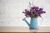 Violet dried flowers in blue tin watering flower pot on wooden table with white brick wall background.
