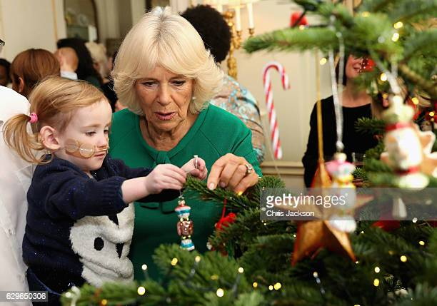 Violet Webster who has a hole in the heart and is aged 2 helps Camilla Duchess of Cornwall decorate the Clarence House Christmas Tree at Clarence...