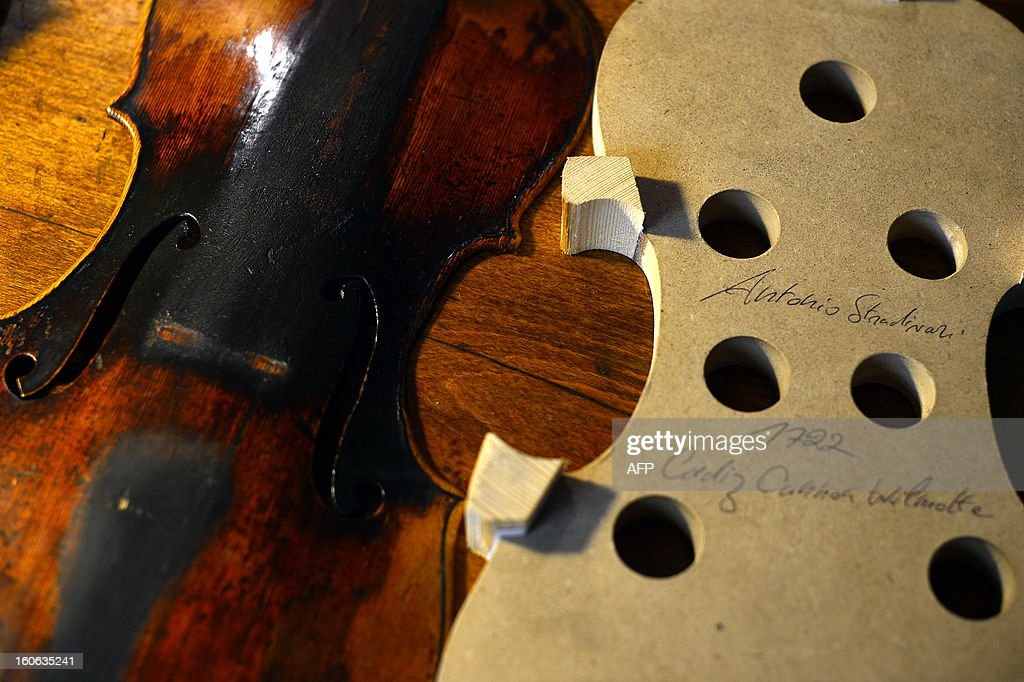 A violin (L) being restored is displayed next to a form in the workshop of Mathias Menanteau, a French violin maker on January 30, 2013 in Rome. After studying and working in England and Germany, Menanteau setup his workshop in the Italian capital, where he builds and restores violins and cellos for notorious musicians.