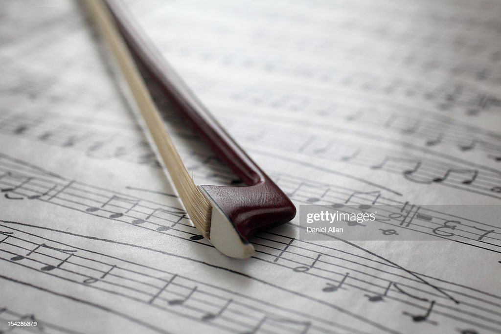 Violin bow on music sheet : Stock Photo