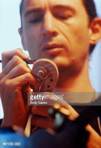 Violin maker adding details to violin : Stock Photo
